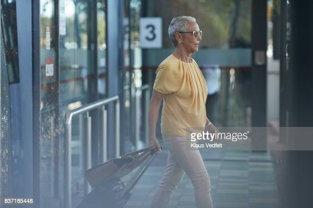 Senior woman walking out of bus, on to public transport platform