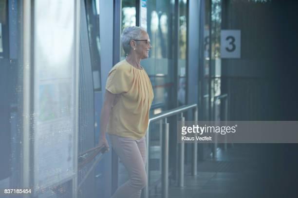 senior woman walking out of bus, on to public transport platform - 降り立つ ストックフォトと画像