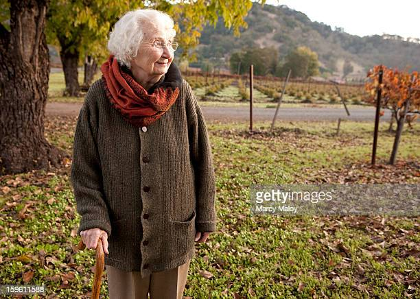 Senior woman walking outdoors with a cane.