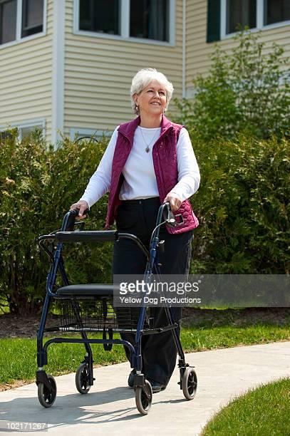 Senior woman walking outdoors with walker