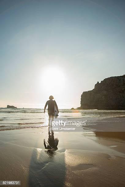 Senior woman walking toward sea with surfboard, Camaret-sur-mer, Brittany, France