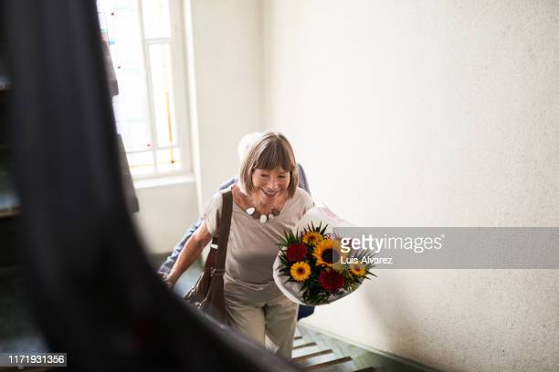 senior woman walking up the stairs with flowers - moving up stock pictures, royalty-free photos & images