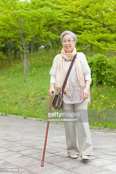Senior woman walking with a cane, Tokyo Prefecture, Honshu, Japan