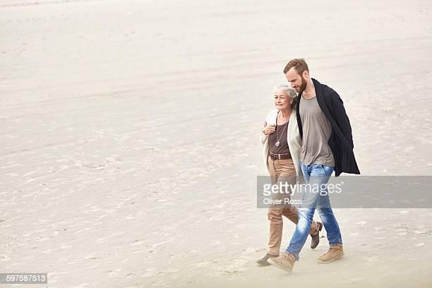 senior woman walking with adult son on the beach - legame affettivo foto e immagini stock