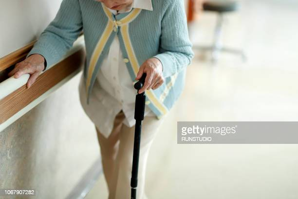senior woman walking with walking cane in hospital corridor - care home stock pictures, royalty-free photos & images