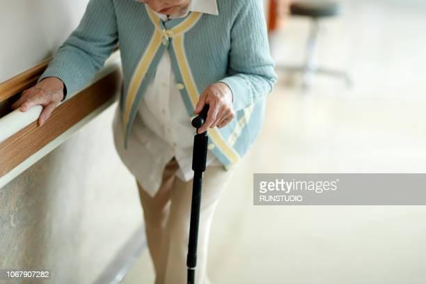 senior woman walking with walking cane in hospital corridor - begeleid wonen stockfoto's en -beelden
