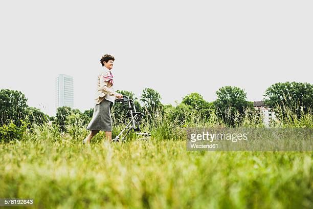 Senior woman walking with wheeled walker