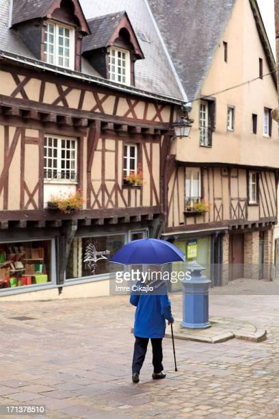 Senior woman walks in Old quarter of Laval, France