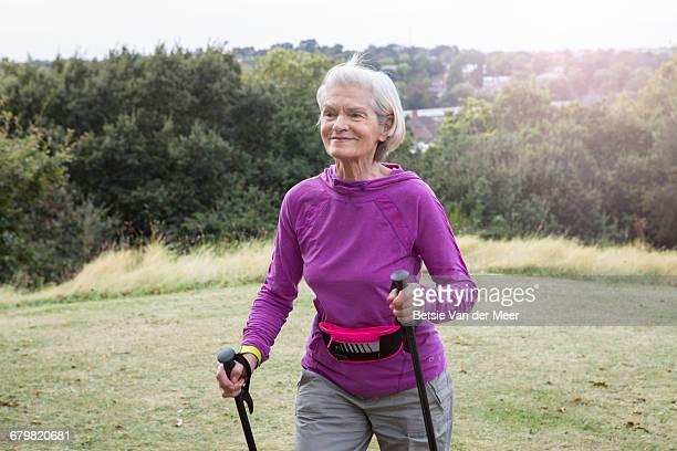 Senior woman walks in park landscape.