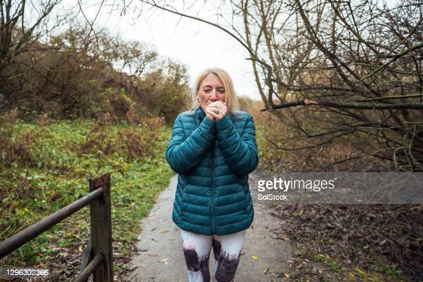 senior woman warming up her hands - cold temperature stock pictures, royalty-free photos & images