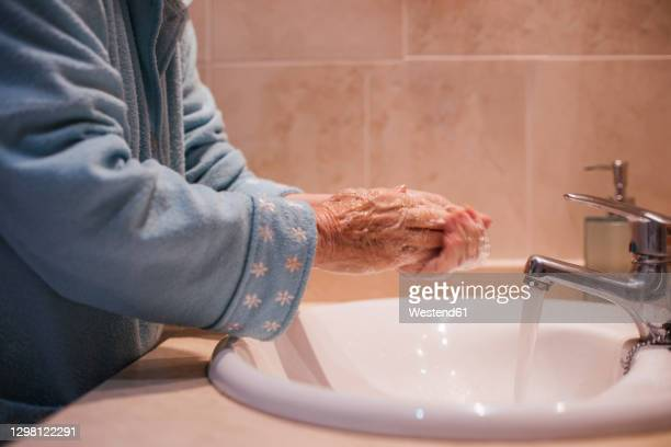 senior woman washing hands by sink at home - flowing water stock pictures, royalty-free photos & images