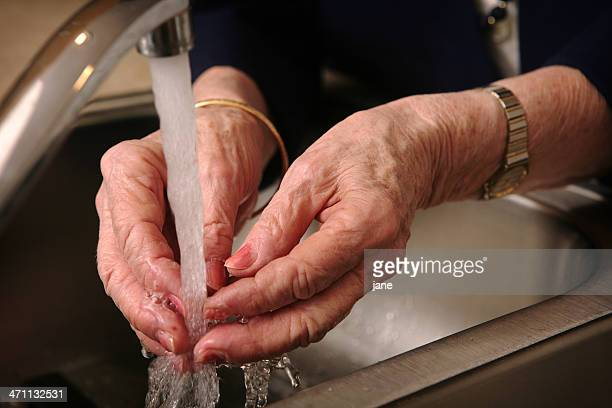 Senior woman washing her hands in metal sink
