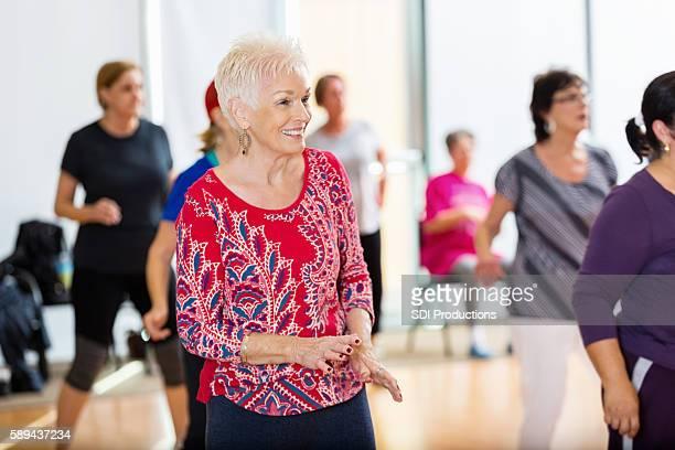 Senior woman watches dance instructor at senior center
