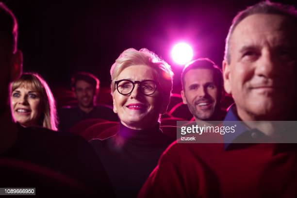 senior woman watching comedy movie in the cinema - divergent film stock photos and pictures