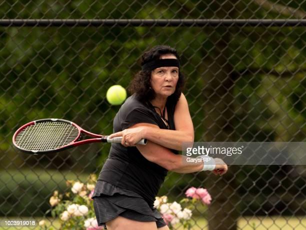 senior vrouw kijken intens na raken tennisbal - linkshandig stockfoto's en -beelden