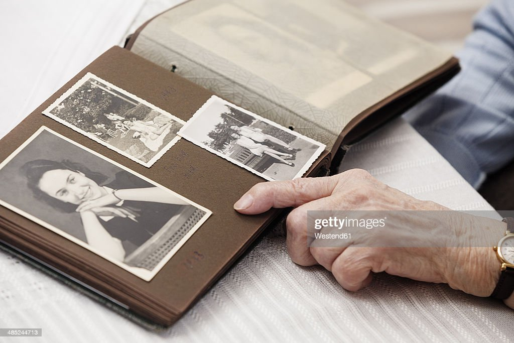 Senior woman watching old photographs of herself : Stock Photo