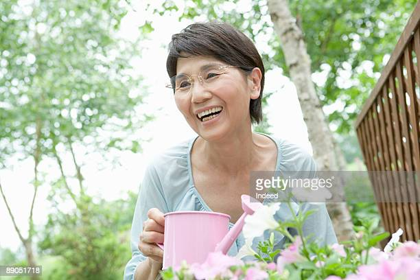 Senior woman watering flowers