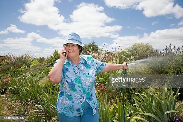 Senior woman watering garden while using mobile phone, smiling