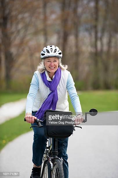 Senior Woman wearing a bike helmet riding bike