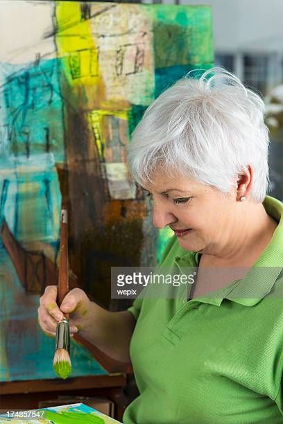 Senior woman wearing a green t-shirt painting in an art studio