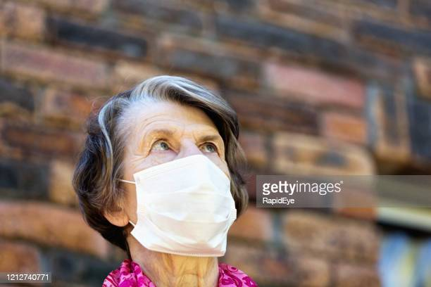 senior woman wearing a mask to avoid infection during the covid-19 coronavirus epidemic - fragility stock pictures, royalty-free photos & images