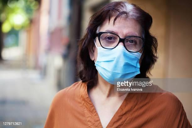 femme aîné utilisant un masque et des lunettes protecteurs - bulgarie photos et images de collection