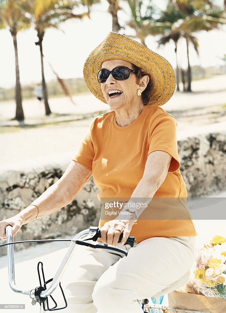 Senior Woman Wearing a Sun Hat and Riding a Bicycle : Stock Photo