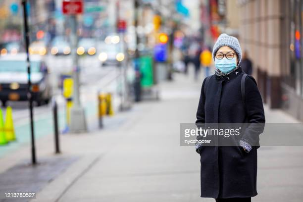 senior woman wearing a surgical mask on the streets of new york city - coronavirus winter stock pictures, royalty-free photos & images