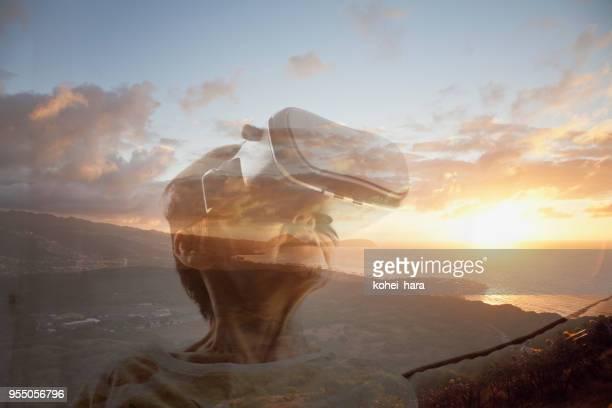 仮想現実のヘッドセットを着て、仮想現実世界ではダイヤモンド ヘッドから風景の夜明けを鑑賞するシニア女性