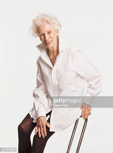 senior woman wearing a white shirt sitting on a stool - old women in pantyhose stock photos and pictures
