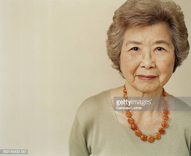 Senior woman wearing amber necklace, portrait