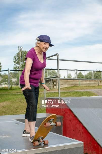 senior vrouw baseballpet te dragen aan de kant klaar om te skateboarden tijdens zomerdag in skatepark - jong van hart stockfoto's en -beelden