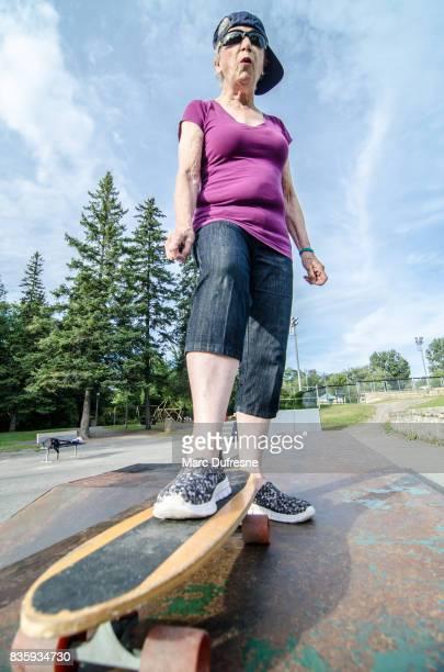 Haute femme portant la casquette de baseball sur le côté prêt à planche à roulettes au cours de la journée d'été dans skate park
