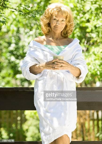 Senior woman wearing bathrobe, holding mug, outdoors