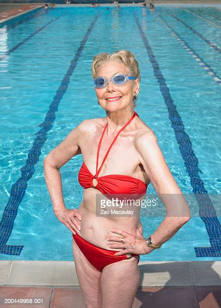 Senior woman wearing bikini and goggles standing by pool, smiling