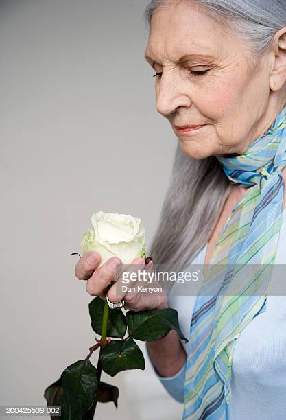 Senior woman wearing blue scarf looking at white rose in hand