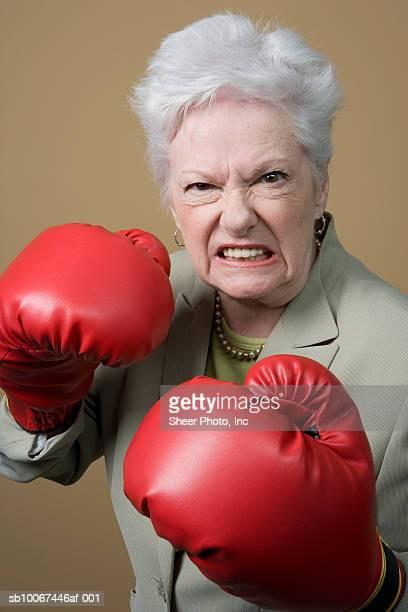 Senior woman wearing boxing gloves, studio shot