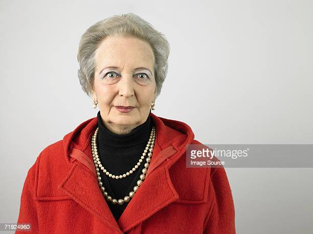 senior woman wearing coat - pearl necklace stock pictures, royalty-free photos & images
