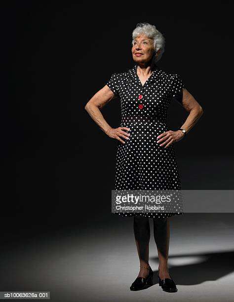 senior woman wearing dress with polka dot pattern standing and looking up - hand on hip stock pictures, royalty-free photos & images