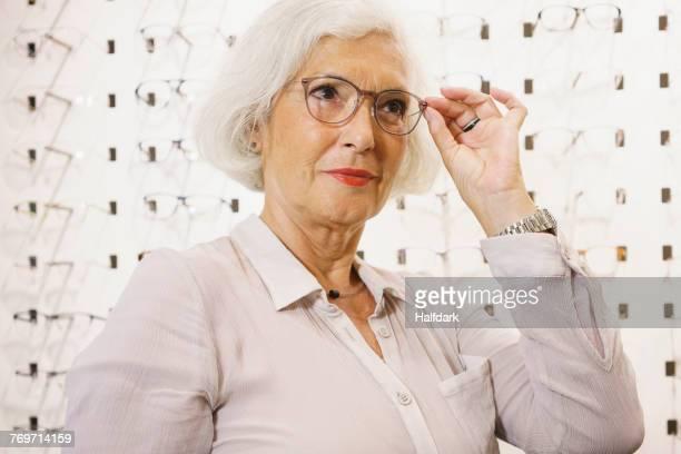 senior woman wearing eyeglasses at store - eine seniorin allein stock-fotos und bilder