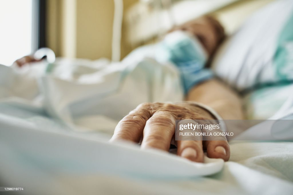 Senior woman wearing face mask lying on hospital bed : Stockfoto