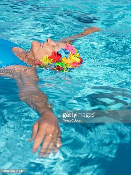 Senior woman wearing floral swimming hat, floating in pool, smiling