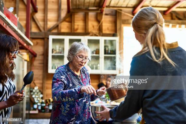 senior woman wearing glasses and holding saucepan - 60 69 anos imagens e fotografias de stock
