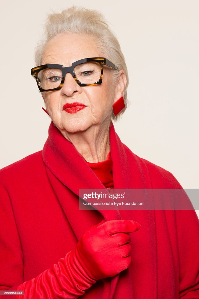 Senior woman wearing glasses and red coat : Stock Photo