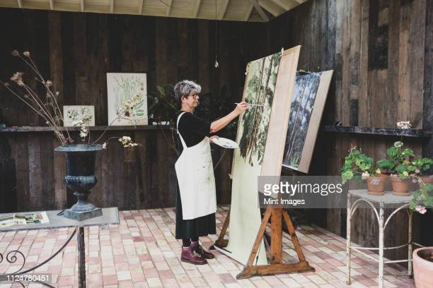 senior woman wearing glasses, black top and apron standing in studio, working on painting of trees in forest. - artist stock pictures, royalty-free photos & images