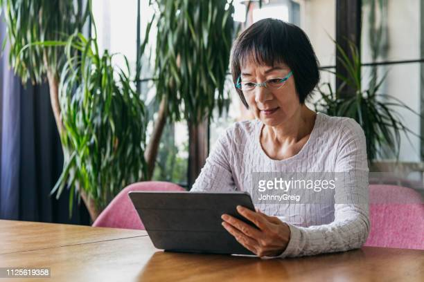 senior woman wearing glasses reading digital tablet - solo 2018 film stock pictures, royalty-free photos & images