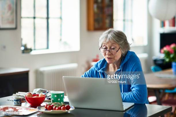 senior woman wearing glasses using laptop at home - 65 69 jahre stock-fotos und bilder
