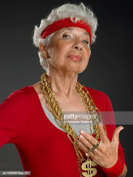 senior woman wearing gold chains with dollar symbol, portrait - bling bling stock pictures, royalty-free photos & images