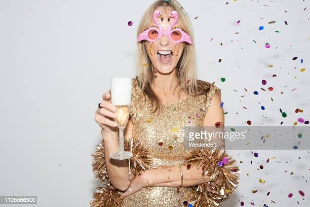 senior woman wearing golden dress and flmingo shaped glasses, celebtraing new year's eve - 63 year old female stock pictures, royalty-free photos & images