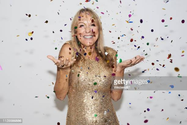 senior woman wearing golden dress, celebtraing new year's eve - celebration stock pictures, royalty-free photos & images